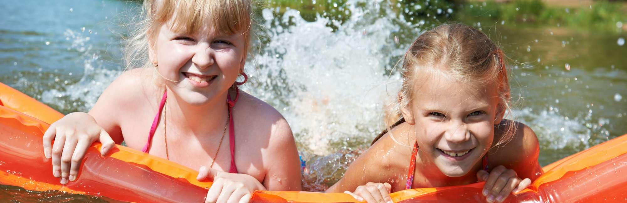 Happy little girls on mattress in lake at summer