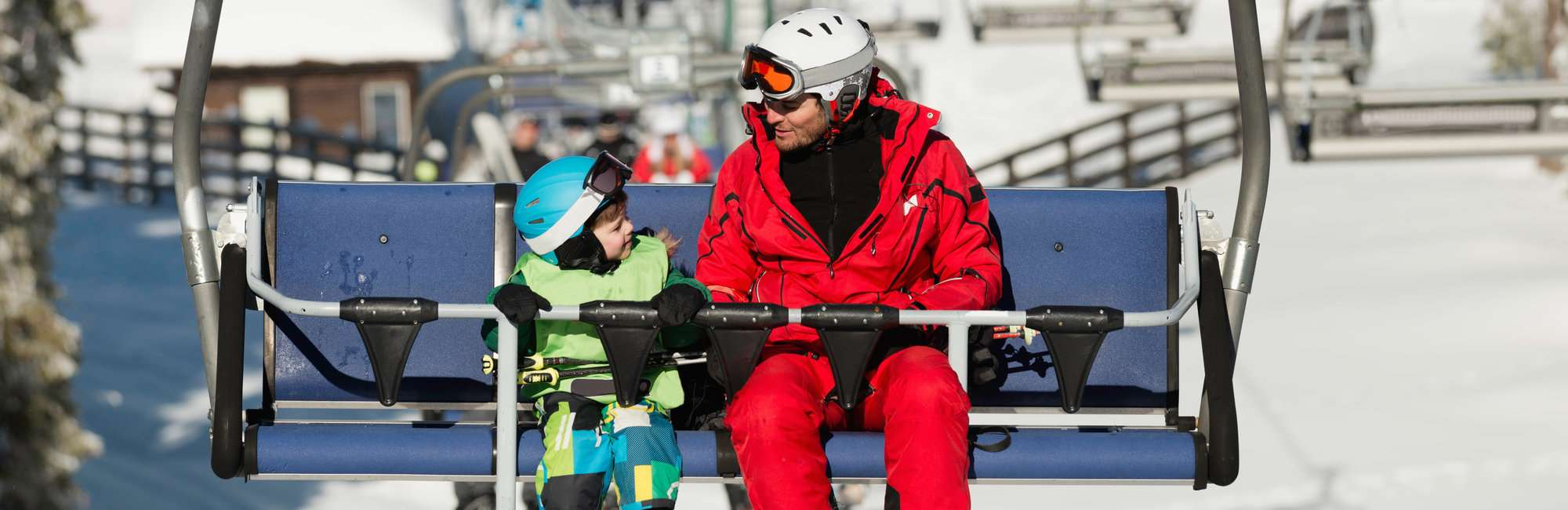 Father and son on ski lift in winter vacation resort