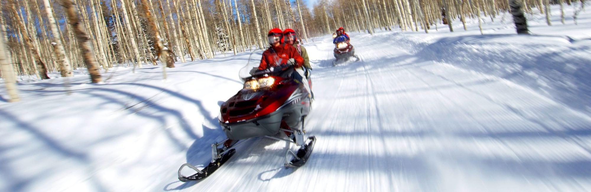 Couples Racing on Snowmobiles