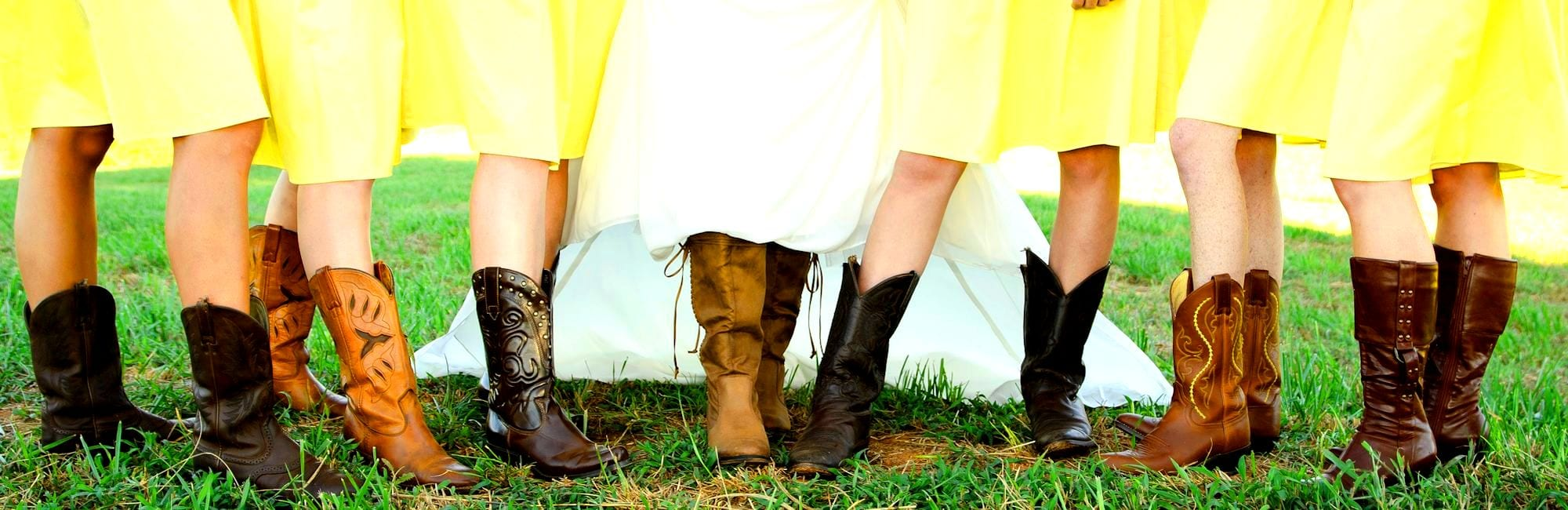 Bride and Bridesmaids show off their boots at a country wedding.