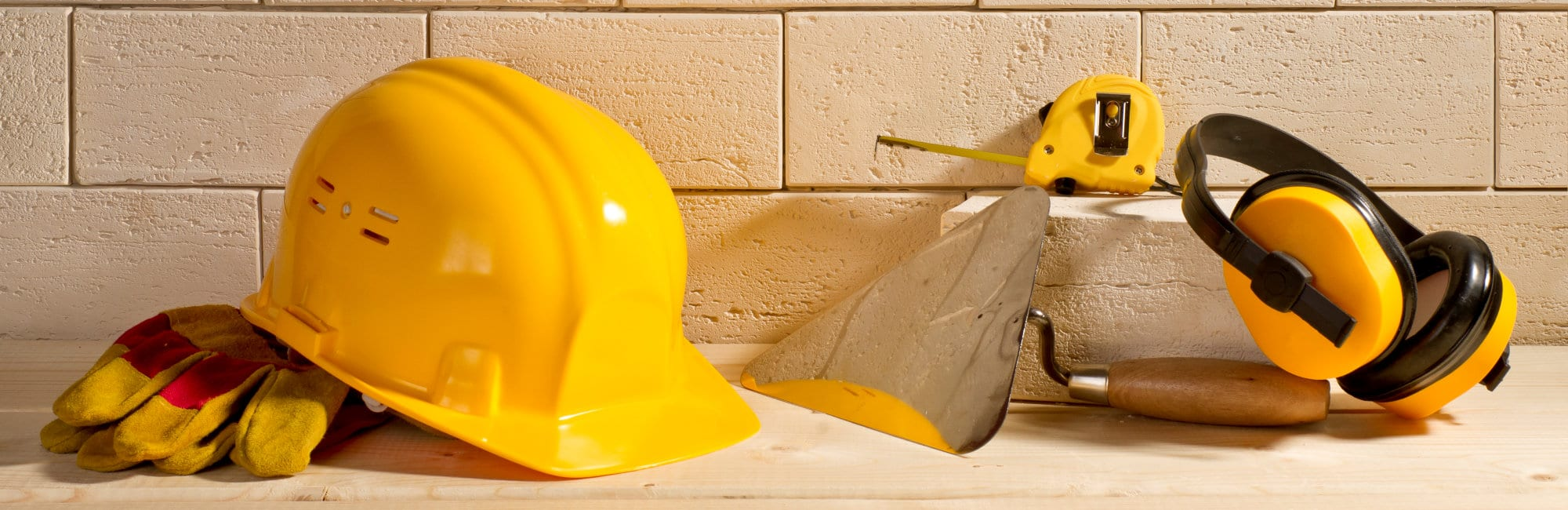 beige brick background, yellow helmet and trowel on a wooden floor